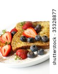 French toast topped with strawberries and blueberries, and a sprinkling of cinnamon. - stock photo