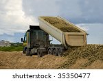 Truck or lorry unloading gravel or rock with lifted loading platform - stock photo