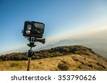 Small photo of Action camera with selfie pole on the peak of mountain