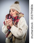 Small photo of Attractive woman warmly dressed in a trendy winter outfit with colorful scarf enjoying a hot cup of coffee as she cradles it in her hands savoring the aroma