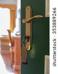 Small photo of Ajar door of a hotel room with an old style copper key number.