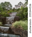 Small photo of Cascading pond in landscaped garden in front of white house in Akureyri, Iceland.