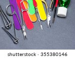 Small photo of Various manicure tools on gray textured surface. Nail clippers, nail and cuticle scissors, colored nail files, double ended cuticle trimmer / pusher, cuticle remover, nail art brushes and nail oil