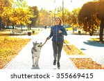 Stock photo happy young woman jogging with her dog in park 355669415
