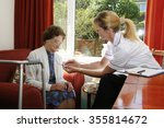 Small photo of An elderly woman being given instruction on the use of an emergency push button medical assistance device by a health worker. 'The old lady is deceased and is my mother'