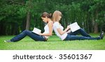 Two young girls sitting on the grass - stock photo