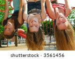 Three young girls hanging upside down in a park and laughing - stock photo