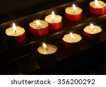 Group Of Lit Votive Candles In...