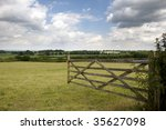 An Open Farm Gate Leading To A...