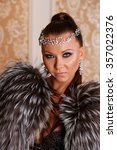 Small photo of Portrait of beautiful girl wearing thiara, lingerie and silver fox fur coat