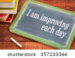 Small photo of I am improving each day - self development concept or positive affirmation on a slate blackboard with a white chalk and a stack of books against rustic wooden table
