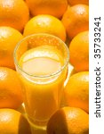 A glass of fresh orange juice and oranges. Macro - stock photo