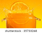 Orange slice falling into juice. Macro - stock photo