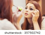 Small photo of Brunette woman applying make up (paint her eyelashes) for a evening date in front of a mirror. Focus on her reflection