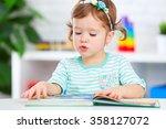 cute baby girl reading a book... | Shutterstock . vector #358127072