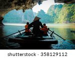 Small photo of Travel in Vietnam,A young girl paddle a bamboo boat for tourist in the beautiful bay.