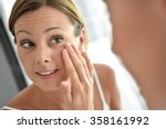 Woman Applying Facial Cream On...