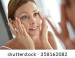 woman applying facial cream on... | Shutterstock . vector #358162082