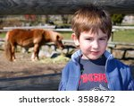 A boy with a pony horse in the background - stock photo