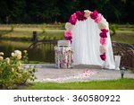 Romantic white wedding aisle archway with rose petals, flowers and a decorated chest. Lake in the background