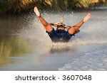 Barefoot water skier on her back with water spray - stock photo