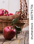 Small photo of Appetizing sweet fresh red apple with green leaves on shank in front of basket full of apples decorated with burlap on wooden table on white wall background, vertical photo