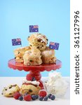Small photo of Happy Australia Day morning tea with fruit scones on red cake stand with fresh fruit and cream on white wood table with blue background, with sample text.