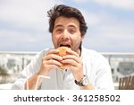 young man eating a hamburger | Shutterstock . vector #361258502