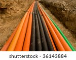 Plastic pipes containing electric cables, in a ditch ready to be filled - stock photo