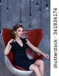 Small photo of beautiful brunette with jewelry sits in a claret chair