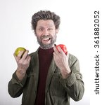 Small photo of Mr. IceMan, smiling man with a beard, beard covered with hoarfrost, man holding apples, he stares at them. fashion man in knitted sweater and jacket.