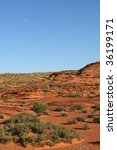 Moon over the afternoon light on the red sandstone landscape - stock photo