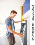 Small photo of man using atm to withdraw cash