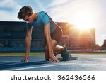 Small photo of Young male athlete at starting block on running track. Young man in starting position for running on sports track. Sprinter about to start a race at stadium with sun flare.