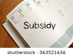 Small photo of Subsidy text concept write on notebook with pen