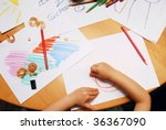 Little hands drawing between school supplies - stock photo