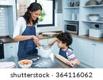 Smiling Mother Cooking With He...