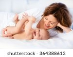 mother and child on a white bed.... | Shutterstock . vector #364388612