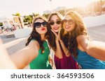 Small photo of Lifestyle sunny image of best friend girls taking selfie on camera, crazy emotions , happy vacations, shopping day. Wearing elegant dress, way hairstyle, sunglasses and red lips.