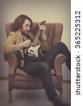 Small photo of Bearded musician playing electric ukulele guitar in vintage chair