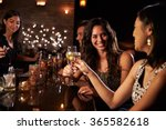 Stock photo female friends enjoying night out at cocktail bar 365582618