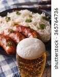 Small photo of Lager beer close-up on a background of snack sausages and sauerkraut. Vertical