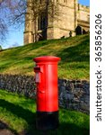 Small photo of WYMESWOLD, ENGLAND - JANUARY 15: A rural British red traditional Royal Mail pillar box. With St Mary's church - behind. In Wymeswold, England on 15th January 2016.