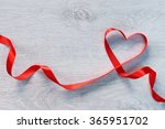 Curved Red Ribbon On A Wooden...