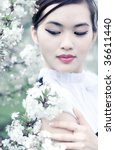 Young woman with cherry flowers. Birght white colors. - stock photo