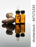 Small photo of Ginger essential oil in amber glass bottle with ginger root and dropper