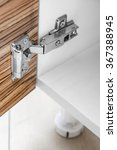 Small photo of Closeup of furniture cabinet modern clip hinge with amortization - kitchen slow motion hardware