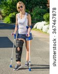 Small photo of Woman wearing an orthopedic leg brace with adjustable straps to immobilise her leg following surgery or an accident walking on crutches outdoors