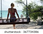 woman on a swing at the sea  | Shutterstock . vector #367734386