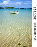 A white boat floating on clear sea, Isles of Scilly, Cornwall. - stock photo